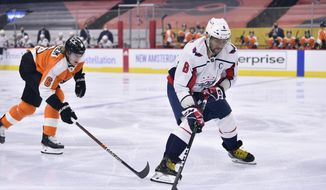 Washington Capitals' Alex Ovechkin, right, skates the puck past Philadelphia Flyers' Travis Sanheim (6) during the first period of an NHL hockey game, Thursday, March 11, 2021, in Philadelphia. (AP Photo/Derik Hamilton)