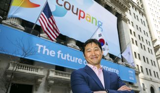 """In this photo provided by the New York Stock Exchange, Coupang Founder and CEO Bom Kim poses in front of the New York Stock Exchange facade before his company's IPO, Thursday march 11, 2021.The biggest IPO in years is rolling out Thursday on the NYSE where Coupang, the South Korean equivalent of Amazon in the U.S., or Alibaba in China, will begin trading under the ticker """"CPNG."""" (Courtney Crow/New York Stock Exchange via AP)"""
