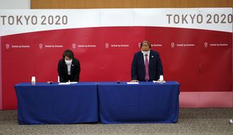 Seiko Hashimoto, left, President of the Tokyo 2020 Organizing Committee of the Olympic and Paralympic Games (Tokyo 2020),  and Toshiro Muto, CEO of Tokyo 2020, bow at the beginning of a news conference Thursday, March 11, 2021, following the International Olympic Committee (IOC) general meeting. (AP Photo/Eugene Hoshiko, Pool)