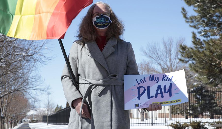 Stephanie Marty demonstrates against a proposed ban on transgender girls and women from female sports leagues outside the South Dakota governor's mansion in Pierre, S.D. on Thursday March 11, 2021. (AP Photo/Stephen Groves)