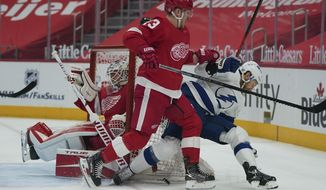 Detroit Red Wings left wing Adam Erne (73) defends Tampa Bay Lightning right wing Barclay Goodrow (19) in the first period of an NHL hockey game Thursday, March 11, 2021, in Detroit. (AP Photo/Paul Sancya)