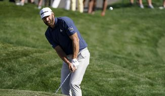 Dustin Johnson chips to the green on the ninth hole during the first round of the The Players Championship golf tournament Thursday, March 11, 2021, in Ponte Vedra Beach, Fla. (AP Photo/John Raoux) **FILE**