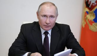 Russian President Vladimir Putin speaks during a meeting via video conference with officials and government cabinet members in Moscow, Russia, Thursday, March 11, 2021. (Alexei Druzhinin, Sputnik, Kremlin Pool Photo via AP)