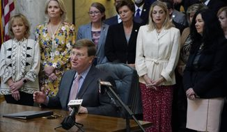Mississippi Gov. Tate Reeves explains to reporters why he signed the first state bill in the U.S. this year to ban transgender athletes from competing on female sports teams, Thursday, March 11, 2021, at the Capitol in Jackson, Miss. From left standing behind Reeves are Rep. Becky Currie, R-Brookhaven, Rep. Jill Ford, R-Madison, Sen. Jenifer Branning, R-Philadelphia, Sen. Rita Potts Parks, R-Corinth, Rep. Dana McLean, R-Columbus and Sen. Angela Burks Hill, R-Picayune, who were among the legislation's supporters who attended the bill signing. (AP Photo/Rogelio V. Solis)