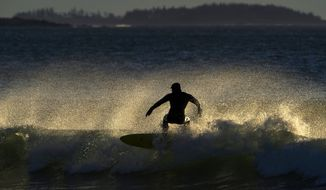 A surfer rides a wind-whipped wave, Friday, March 12, 2021, at Old Orchard Beach, Maine. (AP Photo/Robert F. Bukaty) **FILE**