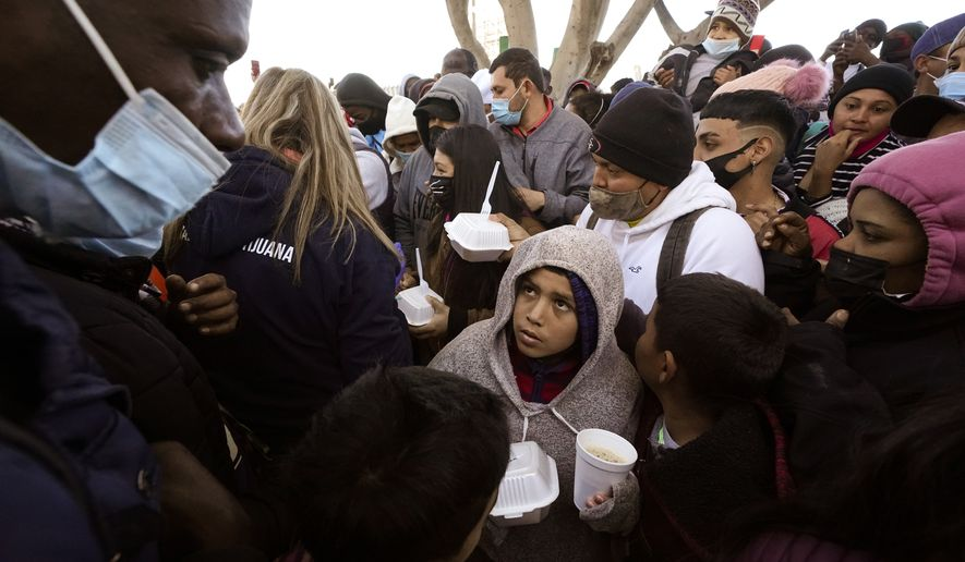 In this Friday, Feb. 19, 2021, file photo, asylum seekers receive food as they wait for news of policy changes at the border, in Tijuana, Mexico. (AP Photo/Gregory Bull, File)