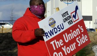 In this Tuesday, Feb. 9, 2021 file photo ,Michael Foster of the Retail, Wholesale and Department Store Union holds a sign outside an Amazon facility where labor is trying to organize workers in Bessemer, Ala. (AP Photo/Jay Reeves, File)  **FILE**