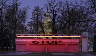 An illuminated traffic barrier is seen on the Capitol grounds before sunrise in Washington, Monday, March 8, 2021. (AP Photo/Carolyn Kaster)