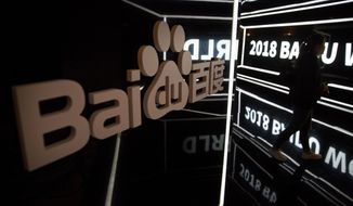 FILE - In this Nov. 1, 2018, file photo, an attendee walks past a display at the 2018 Baidu World conference in Beijing. China's market regulator said Friday, March 12, 2021, that it fined 12 companies, including games company Tencent Holdings and Chinese search engine firm Baidu Inc., for not disclosing past deals as authorities step up scrutiny over anti-monopoly behavior in the internet sector. (AP Photo/Mark Schiefelbein, File)