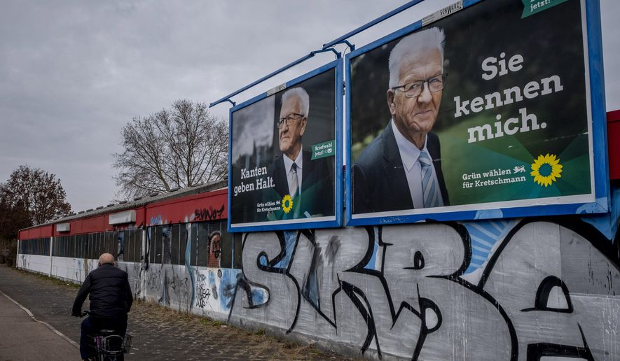 """Election posters show Winfried Kretschmann from the Greens and the party's top candidate for the Baden-Wurttemberg federal state elections in Mannheim, Germany, Wednesday, March 10, 2021. The elections will take place next Sunday. Letters on left poster read """"edges stabilize"""", letters on right poster read """"you know me"""". (AP Photo/Michael Probst)"""