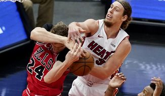 Chicago Bulls forward Lauri Markkanen, left, and Miami Heat forward Kelly Olynyk battle for a rebound during the first half of an NBA basketball game in Chicago, Friday, March 12, 2021. (AP Photo/Nam Y. Huh)