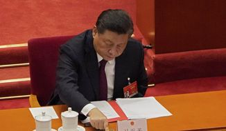 In this Thursday, March 11, 2021, file photo, president Xi Jinping casts his vote during the closing session of the National People's Congress (NPC) at the Great Hall of the People in Beijing.  (AP Photo/Sam McNeil, File)  **FILE**
