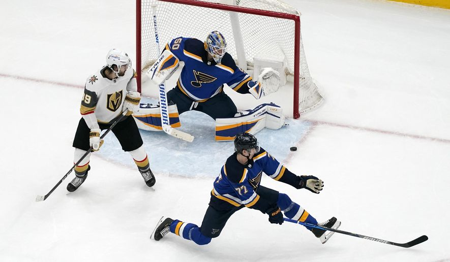 Vegas Golden Knights' Alex Tuch (89) watches as the game-winning goal by teammate Reilly Smith, not shown, slips past St. Louis Blues goaltender Jordan Binnington (50) and Niko Mikkola (77) during overtime of an NHL hockey game Friday, March 12, 2021, in St. Louis. (AP Photo/Jeff Roberson)
