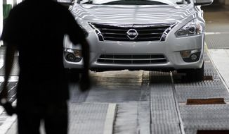FILE - In this May 15, 2012, file photo, a worker walks by a new Nissan Altima on the line after the company celebrated the start of production of the fifth generation of the model at the plant in Smyrna, Tenn. A union wants to hold a vote for representation of fewer than 100 out of thousands of workers at the Nissan vehicle assembly plant in Tennessee, a move the company opposes because the effort doesn't stretch more broadly across the facility's workforce. The National Labor Relations Board began hearing arguments Friday, March 12, 2021, in a case over whether a vote can be held for the subset of employees. (AP Photo/Erik Schelzig, File)