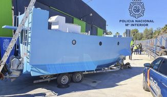 In this photo provided by the Spanish National police on Friday March 12, 2021, a homemade semi submersible submarine sits outside a warehouse in Malaga, Spain. Spanish police say they have seized a homemade narco-submarine able to carry up to 2 metric tons (2.2 tons) of cargo. Police came across the 9-meter-long (30-feet-long) craft being built in Málaga, on southern Spain's Costa del Sol, during a broader international drug operation. Police said Friday it has two 200-horsepower engines, which are operated from the inside. (Police Nacional via AP)