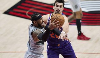 Portland Trail Blazers forward Carmelo Anthony, left, and Phoenix Suns forward Dario Saric vie for a rebound during the second half of an NBA basketball game in Portland, Ore., Thursday, March 11, 2021. (AP Photo/Craig Mitchelldyer)