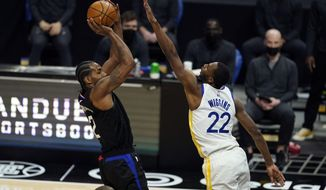 Los Angeles Clippers forward Kawhi Leonard, left, shoots over Golden State Warriors forward Andrew Wiggins (22) during the second half of an NBA basketball game Thursday, March 11, 2021, in Los Angeles. (AP Photo/Marcio Jose Sanchez)