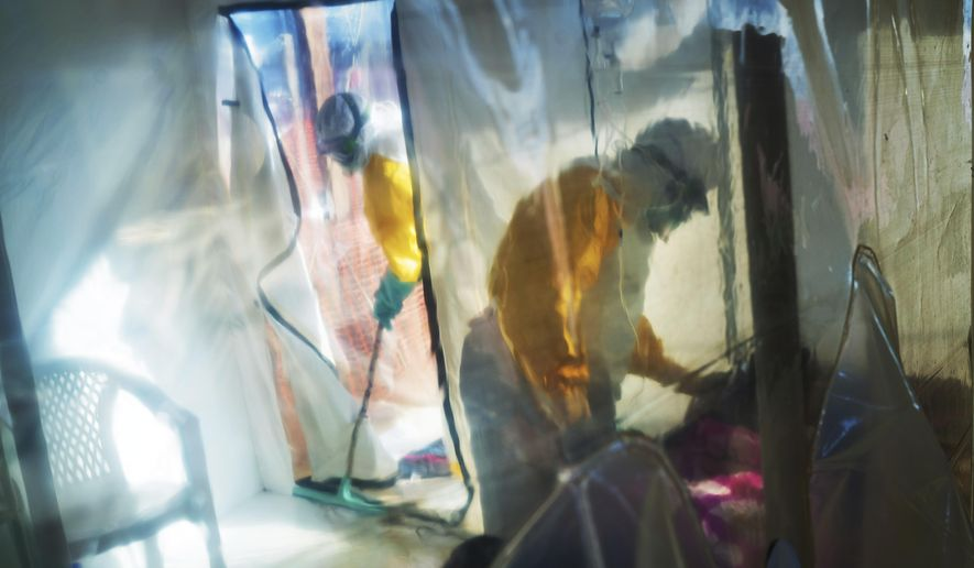 In this Saturday, July 13, 2019, photo, health workers wearing protective suits tend to an Ebola victim kept in an isolation tent in Beni, Democratic Republic of Congo. A top official at the World Health Organization has said on Friday, March 12, 2021 that a genetic analysis of the ongoing Ebola outbreak in Guinea suggests it may have been sparked by a survivor of the devastating West Africa epidemic that ended five years ago. (AP Photo/Jerome Delay) **FILE**