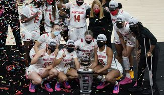 The Maryland team celebrates with the trophy after defeating Iowa in an NCAA college basketball championship game at the Big Ten Conference tournament, Saturday, March 13, 2021, in Indianapolis. Maryland won 104-84. (AP Photo/Darron Cummings)