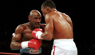"""FILE - In this April 1987 file photo, """"Marvelous"""" Marvin Hagler, left, moves in on """"Sugar"""" Ray Leonard during the third round of a boxing bout in Las Vegas. Leonard won with a split decision. Hagler, the middleweight boxing great whose title reign and career ended with the loss to Leonard in 1987, died Saturday, March 13, 2021. He was 66. (AP Photo/Lennox McLendon, File)"""