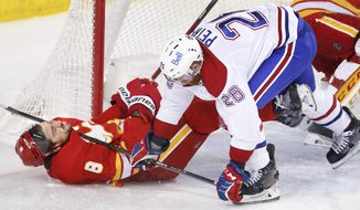 Montreal Canadiens' Jeff Petry, right, knocks down Calgary Flames' Christopher Tanev during the first period of an NHL hockey game in Calgary, Alberta, Saturday, March 13, 2021. (Larry MacDougal/The Canadian Press via AP)