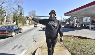 """Joe Jones waves as he is recognized by a neighbor outside the Exxon gas station in his Southwest DeKalb neighborhood on Wednesday, Feb. 24, 2021. Joe Jones launched a protest and boycott of the Exxon gas station in his Southwest DeKalb neighborhood after a clerk told one customer he """"didn't give a f--- about the black community"""" and the owner called him a """"food stamp cockroach."""" They protested outside the store for 66 days -- and it worked. the owner agreed to sell. (Hyosub Shin/Atlanta Journal-Constitution via AP)"""