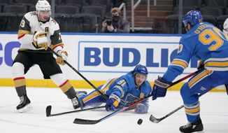 Vegas Golden Knights' Reilly Smith (19) watches as St. Louis Blues' Vladimir Tarasenko (91) and Ryan O'Reilly, right, reach for a loose puck during the second period of an NHL hockey game Saturday, March 13, 2021, in St. Louis. (AP Photo/Jeff Roberson)