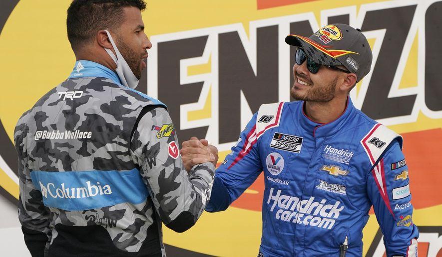 Bubba Wallace, left, congratulates Kyle Larson after Larson won a NASCAR Cup Series auto race Sunday, March 7, 2021, in Las Vegas. (AP Photo/John Locher)