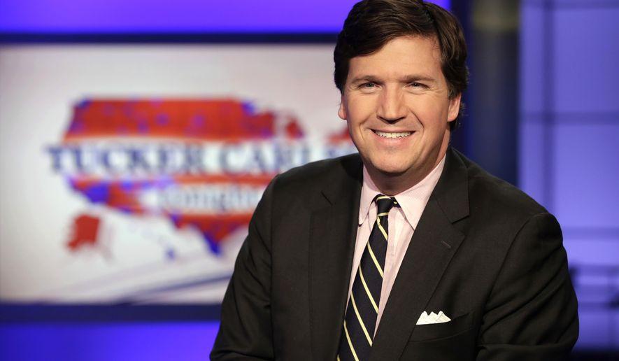 "Tucker Carlson, host of ""Tucker Carlson Tonight,"" poses for photos in a Fox News Channel studio, in New York. (AP Photo/Richard Drew)"