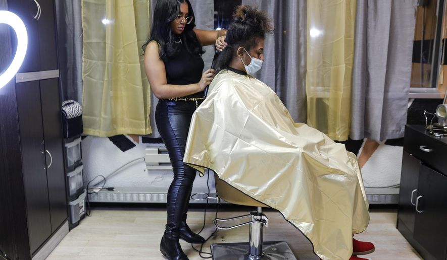 Shaynae Clark works with client Sharnay Reed of Inkster at the Luxury Beauty Experience Salon, Spa & Beauty Store in Southfield, Wednesday, Nov. 18, 2020. Clark opened The Luxury Beauty Experience Salon, Spa & Beauty Store in Southfield, a business in which she sells wig hats, runs a hair salon and continues to create hair products.(Junfu Han/Detroit Free Press via AP)