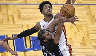 Miami Heat forward KZ Okpala (4) blocks a shot by Orlando Magic guard Michael Carter-Williams (7) during the second half of an NBA basketball game on Sunday, March 14, 2021, in Orlando, Fla. (AP Photo/Phelan M. Ebenhack)
