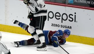 Colorado Avalanche left wing Matt Calvert, right, reaches past Los Angeles Kings defenseman Sean Walker, left, to regain control of the puck in the first period of an NHL hockey game Sunday, March 14, 2021, in Denver. (AP Photo/David Zalubowski)