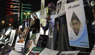 """FILE - In this Feb. 14, 2018 file photo, opposition activist Bader al-Dahoum, left, speaks amid posters that show some of those detained with a hashtag in Arabic reading, """"With Heads Held High,"""" during a protest near Kuwait's parliament in Kuwait City, Kuwait. On Sunday, March 14, 2021, Kuwait's constitutional court ordered al-Dahoum expelled from parliament citing an old conviction for insulting the late emir. The move inflamed tensions between the government and legislature, revealing the limits of political freedom in the Gulf state. (AP Photo/Jon Gambrell, File)"""