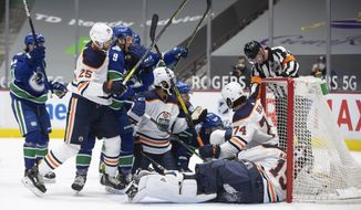 Edmonton Oilers' Darnell Nurse (25) grabs Vancouver Canucks' J.T. Miller (9) after Bo Horvat (53) scored against Edmonton goalie Mikko Koskinen (19) during the second period of an NHL hockey game Saturday, March 13, 2021, in Vancouver, British Columbia. (Darryl Dyck/The Canadian Press via AP)