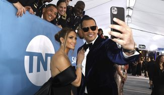 In this Jan. 19, 2020, file photo, Jennifer Lopez, left, and Alex Rodriguez take a selfie as they arrive at the 26th annual Screen Actors Guild Awards at the Shrine Auditorium & Expo Hall  in Los Angeles. (Photo by Matt Sayles/Invision/AP, File)