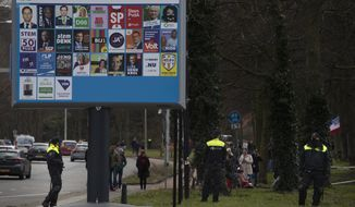 Police block the access for demonstrators next to an election billboard during a rally, ahead of three days of voting starting Monday in a general election, to protest government policies including the curfew, lockdown and coronavirus related restrictions in The Hague, Netherlands, Sunday, March 14, 2021. (AP Photo/Peter Dejong)