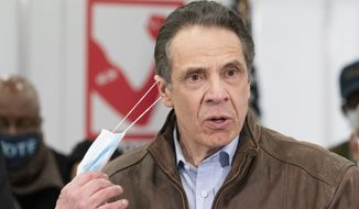 New York Gov. Andrew Cuomo removes his mask during a visit to a COVID-19 vaccination site, Monday, March 15, 2021, at the State University of New York in Old Westbury. (AP Photo/Mark Lennihan, Pool)