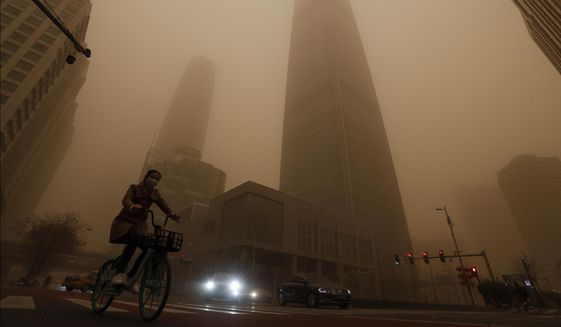 A cyclist and motorists move past office buildings amid a sandstorm during the morning rush hour in the central business district in Beijing, Monday, March 15, 2021. The sandstorm brought a tinted haze to Beijing's skies and sent air quality indices soaring on Monday. (AP Photo/Andy Wong)