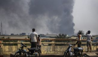 Black smoke billows from the industrial zone of Hlaing Thar Yar township in Yangon, Myanmar Sunday, March 14, 2021. Attacks on Chinese-run factories in Myanmar's biggest city drew demands Monday from Beijing for protection for their property and employees, while many in Myanmar expressed outrage over China's apparent lack of concern for those killed in protests against last month's military coup. Myanmar state media have reported that martial law was declared in six districts in Yangon, including the major industrial zones of Hlaing Thar Yar and Shwepyitha. (AP Photo)