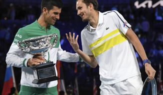 Serbia's Novak Djokovic, left, holds the Norman Brookes Challenge Cup as he talks with runner-up Russia's Daniil Medvedev after winning the men's singles final at the Australian Open tennis championship in Melbourne, Australia, Sunday, Feb. 21, 2021.(AP Photo/Andy Brownbill)