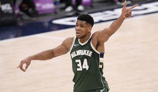 Milwaukee Bucks forward Giannis Antetokounmpo (34) points during the first half of an NBA basketball game against the Washington Wizards, Monday, March 15, 2021, in Washington. (AP Photo/Nick Wass)
