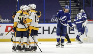 Members of the Nashville Predators, left, celebrate a goal as Tampa Bay Lightning goaltender Curtis McElhinney (35) and Mikhail Sergachev, of Russia, react during the second period of an NHL hockey game Monday, March 15, 2021, in Tampa, Fla. (AP Photo/Mike Carlson)