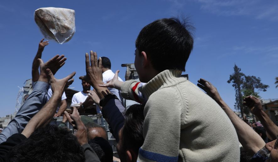 FILE - In this April 16, 2018 file photo, Syrian authorities distribute bread, vegetables and pasta to residents in the town of Douma, near Damascus, Syria. As Syria marks the 10th anniversary Monday, March 15, 2021, of the start of its uprising-turned-civil war, President Bashar Assad may still be in power, propped up by Russia and Iran. But millions of people are being pushed deeper into poverty, and a majority of households can hardly scrape together enough to secure their next meal. (AP Photo/Hassan Ammar, File)