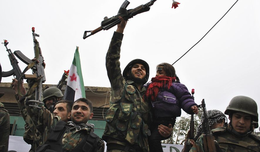FILE - In this Thursday, Jan. 26, 2012, file photo, Syrian army defectors, celebrate shortly after they defected and join the anti-Syrian regime protesters at Khaldiyeh area in Homs province, central Syria. Syrians are marking 10 years since peaceful protests against President Bashar Assad's government erupted in March 2011, touching off a popular uprising that quickly turned into a full-blown civil war. (AP Photo, File)