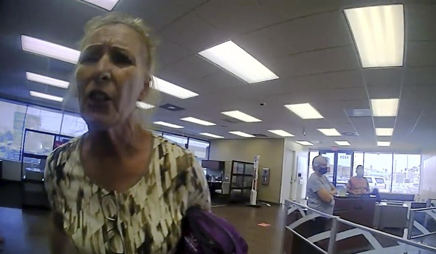 This frame grab from police body cam video provided by the Galveston Police Department, in Galveston, Texas, shows Terry Wright, 65, of Grants Pass, Oregon, arguing with an officer inside a Bank of America branch, Thursday, March 11, 2021, in Galveston, after being told she needed to leave the bank because she was not wearing a face mask, amid the coronavirus pandemic. (Galveston Police Department via AP) ** FILE **