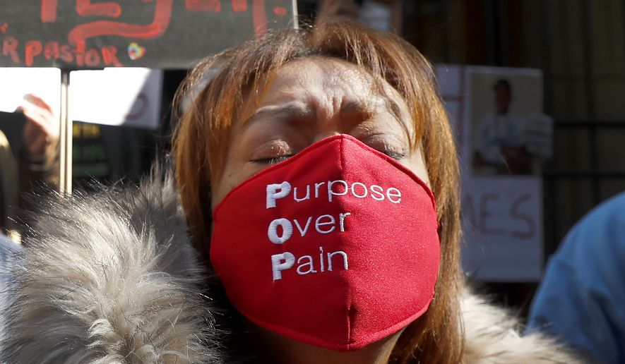 A member of St. Sabina Catholic Church wears a face mask in support of Father Michael Plfeger as she takes part in a rally outside the Archdiocesan Pastoral Center in Chicago demanding resolution of the investigation into allegations against Pfleger Wednesday, Feb. 10, 2021, in Chicago. (AP Photo/Shafkat Anowar)