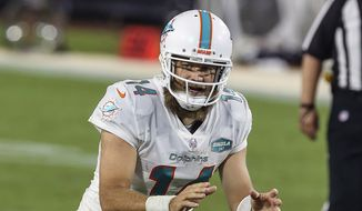 Miami Dolphins quarterback Ryan Fitzpatrick (14) waits for the snap during the second half of an NFL football game against the Jacksonville Jaguars in Jacksonville, Fla., in this Thursday, Sept. 24, 2020, file photo. Ryan Fitzpatrick has agreed to sign a one-year deal with Washington, according to a person with direct knowledge of the move. The person spoke to The Associated Press on condition of anonymity Tuesday, March 16, 2021, because the deal cannot be official until the new league year starts Wednesday. (AP Photo/Gary McCullough, File) **FILE**