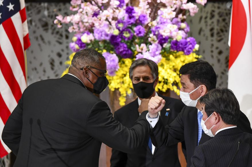 U.S. Defense Secretary Lloyd Austin, left, elbow bumps with Japanese Defense Minister Nobuo Kishi as U.S. Secretary of State Antony Blinken, center, and  Japan's Foreign Minister Toshimitsu Motegi, front, watch after a joint news conference after their two plus two security talks at Iikura Guest House in Tokyo Tuesday, March 16, 2021. Defense and foreign ministers from the U.S. and Japan are meeting to discuss their concern over China's growing influence in the Indo-Pacific region as the Biden administration tries to reaffirm engagement with its key regional allies.(Kazuhiro Nogi/Pool Photo via AP)