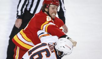 Edmonton Oilers' Jujhar Khaira, right, takes a punch on the chin while fighting Calgary Flames' Brett Ritchie during the first period of their NHL hockey game in Calgary, Monday, March 15, 2021. (Jeff McIntosh/The Canadian Press via AP)