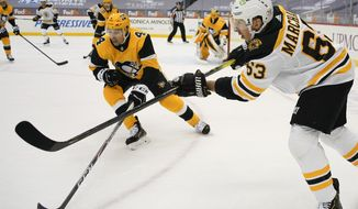 Boston Bruins' Brad Marchand (63) watches after passing there puck past Pittsburgh Penguins' Cody Ceci (4) during the second period of an NHL hockey game, Tuesday, March 16, 2021, in Pittsburgh. (AP Photo/Keith Srakocic)